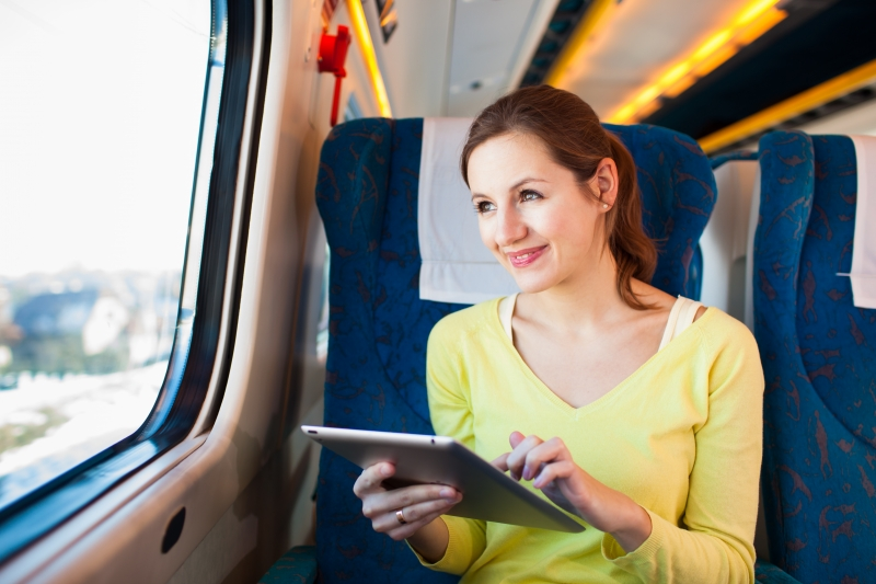 8698339-young-woman-using-her-tablet-computer-while-traveling-by-train